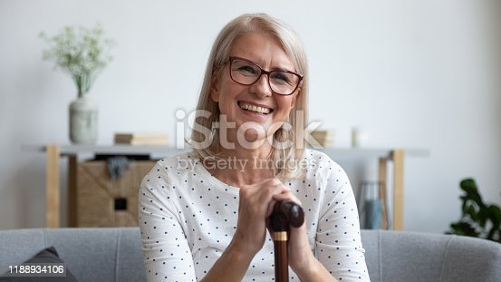Happy old mature adult woman hold cane walking stick sit on sofa looking at camera, smiling senior retired middle aged grandmother satisfied with osteoporosis disease medical treatment, portrait