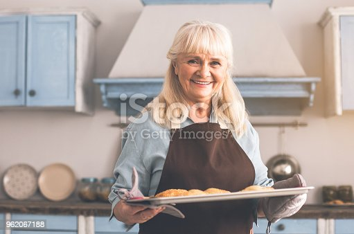 istock Happy old woman holding tray with cookies 962067188