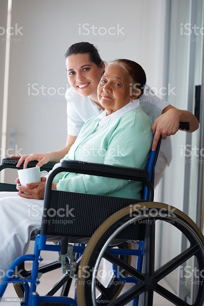 Happy old woman on wheelchair with a nurse royalty-free stock photo