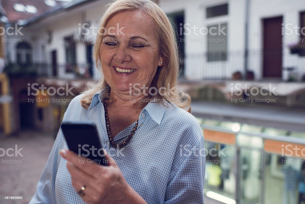 Happy old woman text messaging on mobile phone outdoors. Happy senior woman reading a text message on cell phone outdoors. 2015 Stock Photo