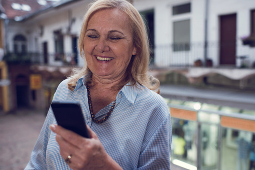 Happy Old Woman Text Messaging On Mobile Phone Outdoors Stock Photo - Download Image Now