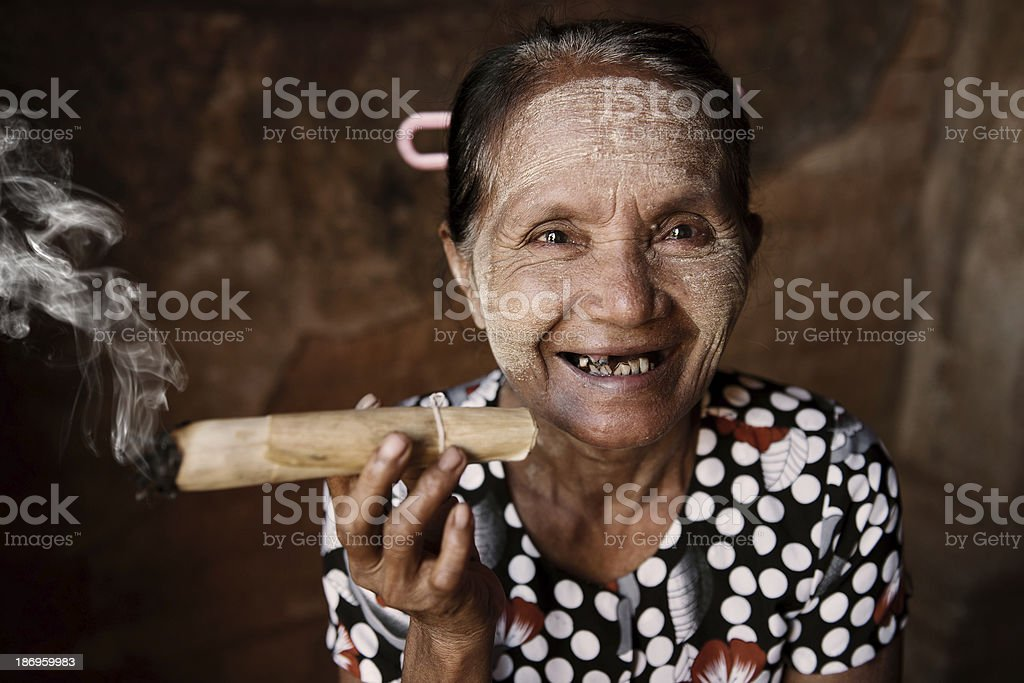 Happy old wrinkled Asian woman smoking stock photo