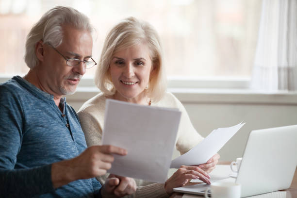Happy older aged couple holding reading good news in document Happy old middle aged couple holding reading good news in document, smiling senior mature family excited by mail letter, checking paying domestic bills online on laptop, discussing budget planning plan document stock pictures, royalty-free photos & images