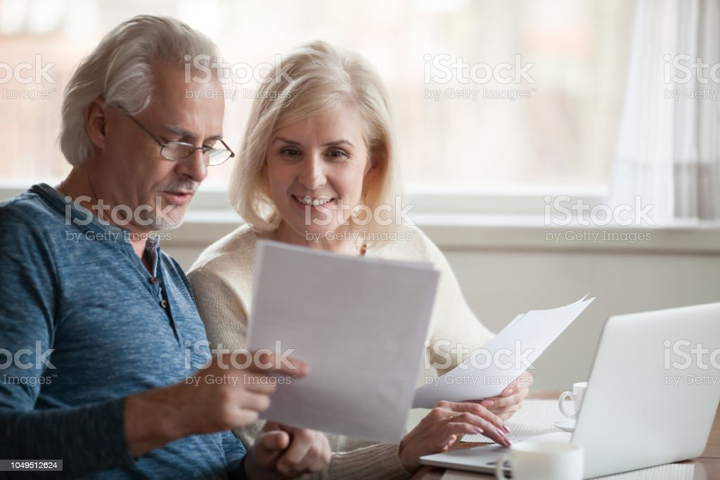 Happy older aged couple holding reading good news in document stock photo