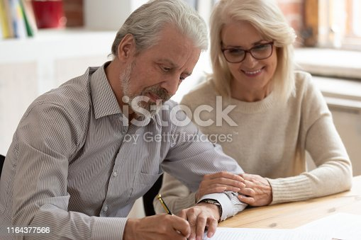 Happy older family couple husband and wife sign legal paper insurance contract write will testament, senior clients customers put signature on business document make financial deal take bank loan