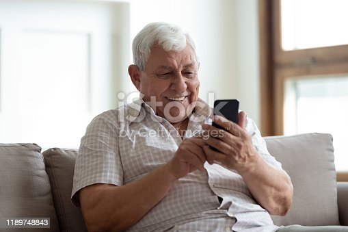 istock Happy older man sitting on sofa at home, using smartphone. 1189748843