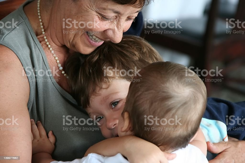 Happy older woman embraces a little boy and a toddler royalty-free stock photo