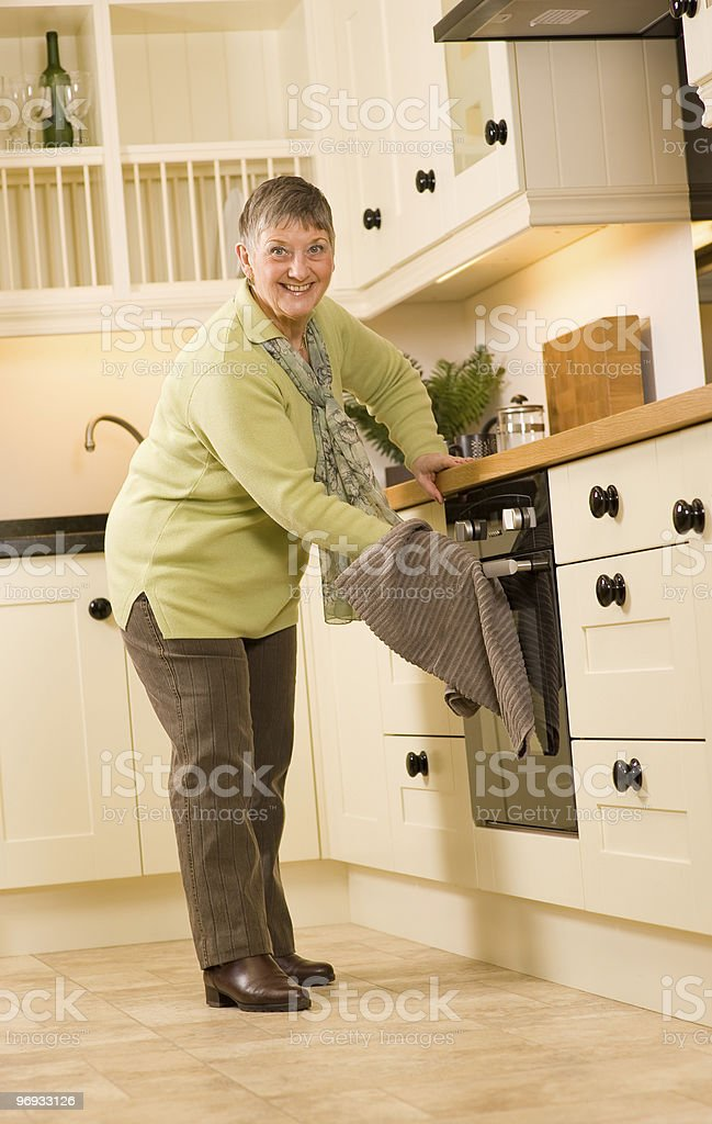 Happy older woman is designer kitchen royalty-free stock photo