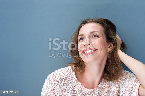 istock Happy older woman laughing with hand in hair 469155178