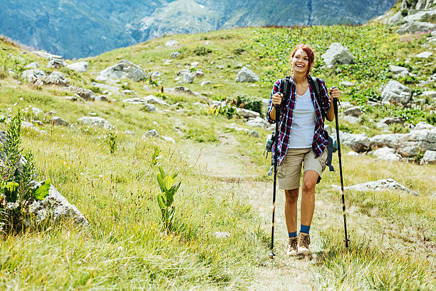 Happy on the mountain footpath Young woman backpacker walking on a footpath in the mountain, copy space. nordic walking stock pictures, royalty-free photos & images