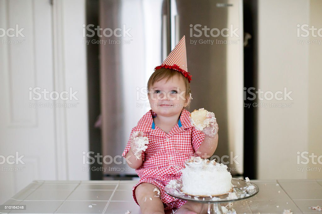 Happy One Year Old Baby Smahing a Cake stock photo