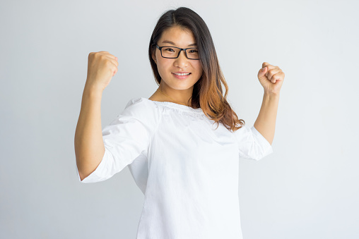 istock Happy optimistic young Asian woman in eyeglasses showing her power 946490868