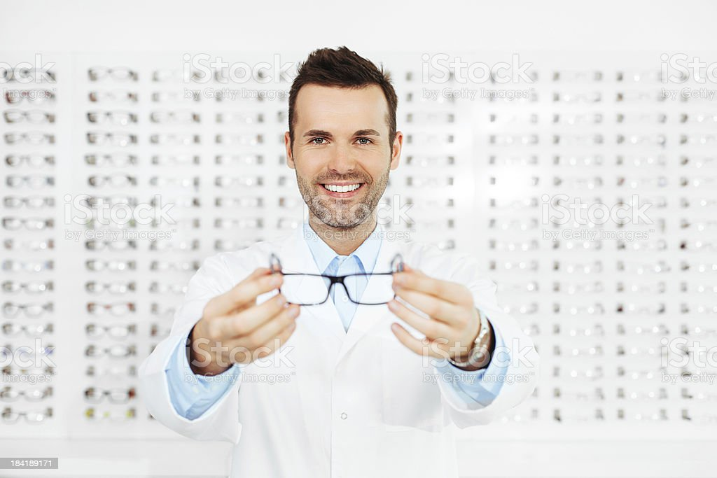 Happy optometrist showing a pair of sight glasses to client stock photo
