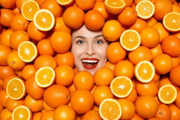 happy orange woman high angle view of happy woman portrait laughing, surrounded by oranges. surrounding stock pictures, royalty-free photos & images