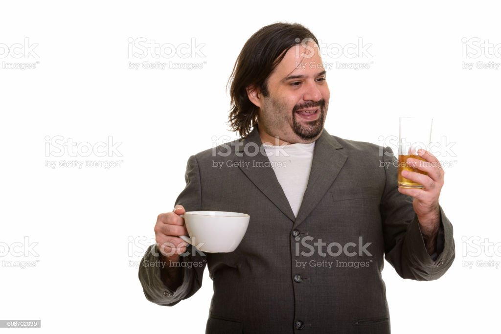 Happy fat bearded businessman smiling while choosing glass of beer over coffee stock photo