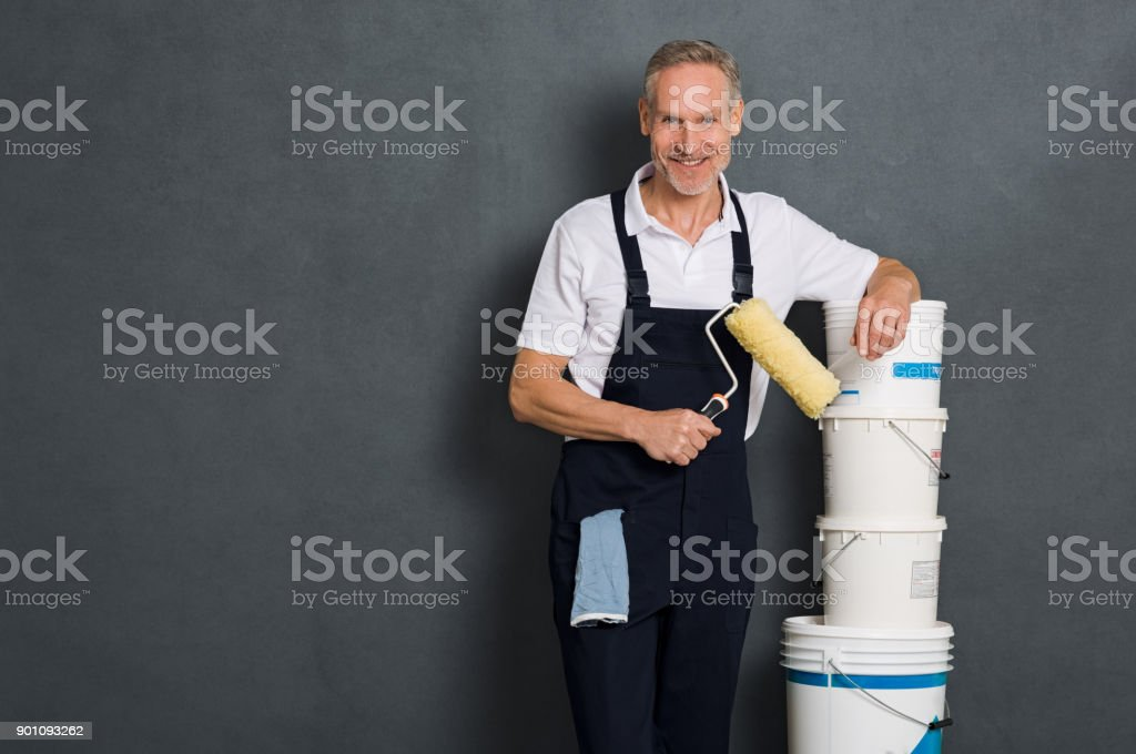 Happy painter holding roller stock photo