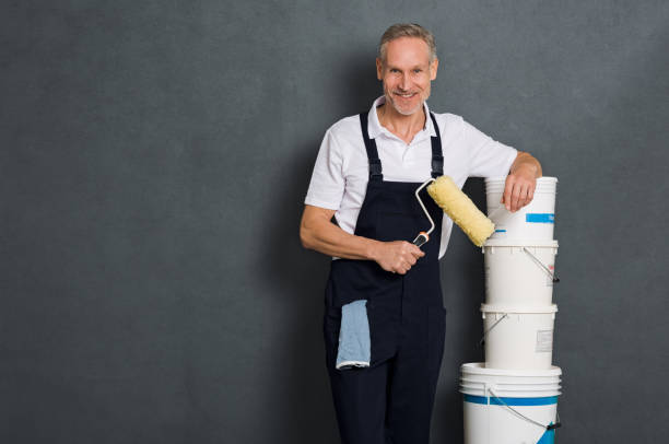 happy painter holding roller - painter stock photos and pictures