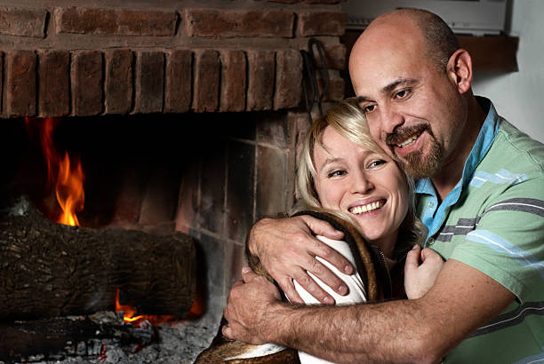 Happy pair near a fireplace in winter evening stock photo