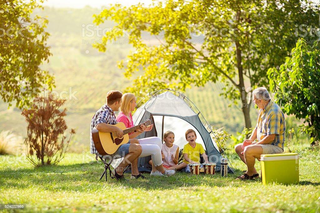 happy parent and children enjoying camping stock photo