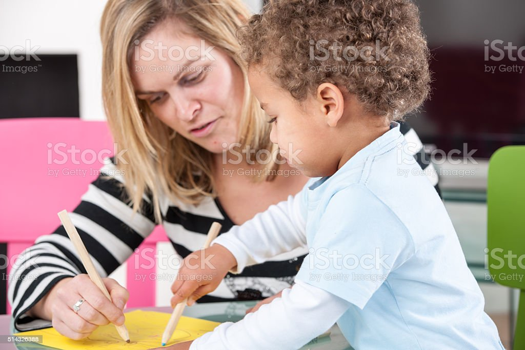 Happy Parent/ Carer/ Childminder Enjoying Artwork With Toddler A close-up of a happy  parent/ carer/ childminder enjoying drawing with toddler/ son in the living room. 2-3 Years Stock Photo