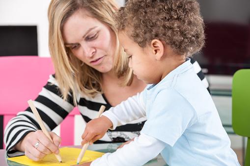 Happy Parent Carer Childminder Enjoying Artwork With Toddler Stock Photo - Download Image Now