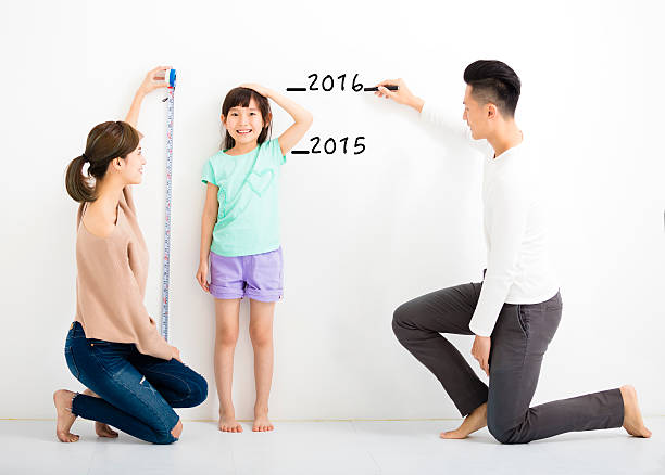 happy parent measures the growth of   daughter - height measurement stock photos and pictures