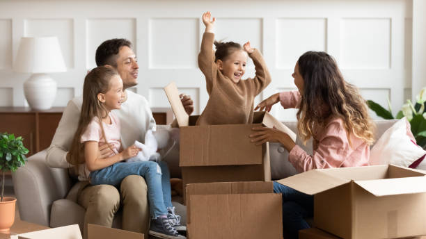 Happy parents and children playing on moving day unpacking boxes Happy family parents and children tenants renters new home owners playing on moving day unpacking boxes, cute little child daughter jump out of box enjoying relocation into own house concept physical activity stock pictures, royalty-free photos & images