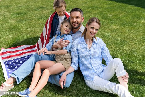 istock Happy parents and children relaxing on grass with american flag, celebrating 4th july - Independence Day 802428804