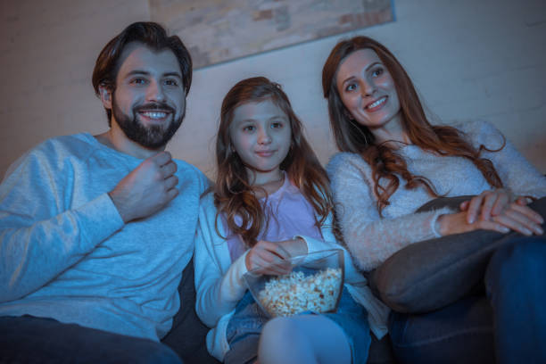 glückliche eltern und tochter vor dem fernseher mit popcorn - mädchen night snacks stock-fotos und bilder