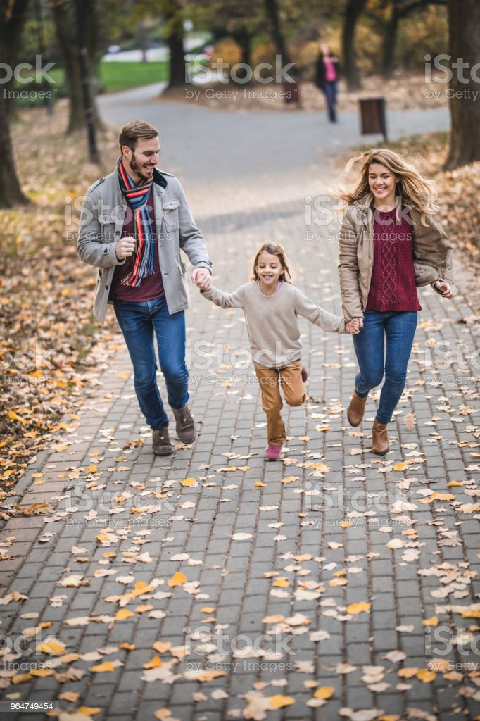 Happy parents and their daughter having fun while running in the park. royalty-free stock photo