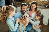 istock Happy parents and their daughters having fun with a dog at home. 1215369368