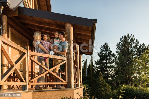 Young happy family talking while enjoying in their time on a terrace of their chalet.