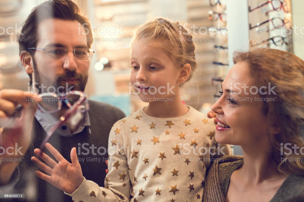 Happy parents choosing eyeglasses for their small daughter at optician store. stock photo