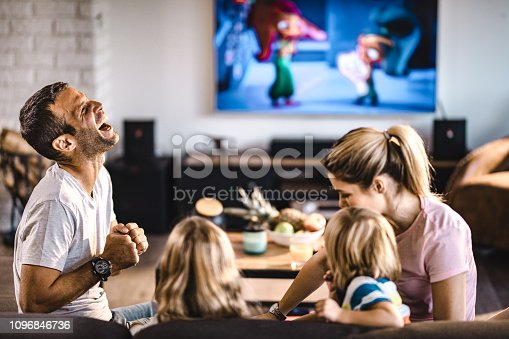 1159543952istockphoto Happy parents having fun with their kids in the living room. 1096846736