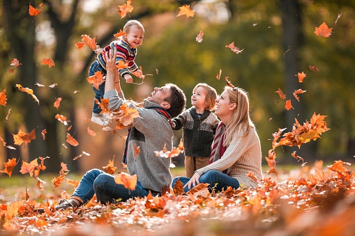Young playful family having fun in autumn day at the park.