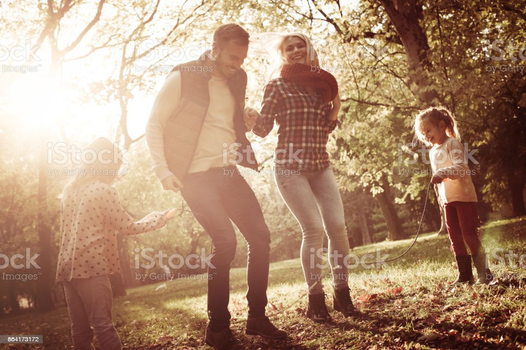 Happy parents jumping across jump rope and their daughters holding rope. royalty-free stock photo