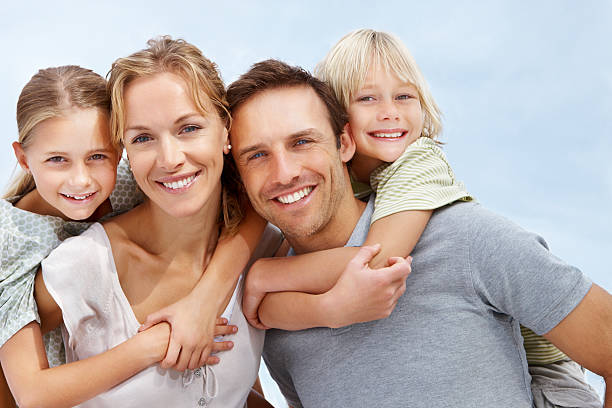happy parents piggybacking their children - four people stock photos and pictures