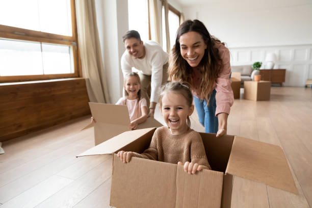 Happy parents playing with little kids riding in box Happy parents playing with cute small kids daughters laughing on moving day, family tenants renters homeowners and children girls having fun riding in box in living room relocating new home concept physical activity stock pictures, royalty-free photos & images
