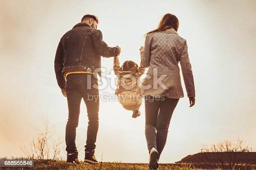658444674istockphoto Happy parents playing with their daughter in the park. Parents raise in the air a little girl. 688955846