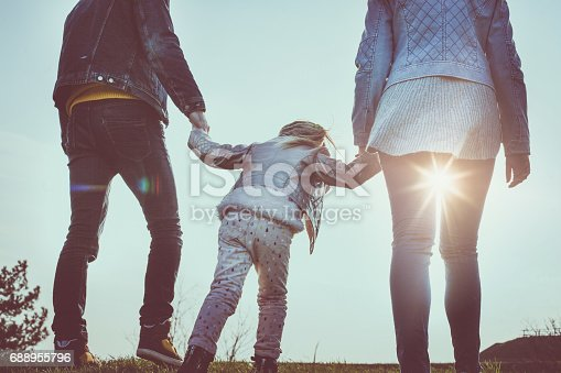 658444674istockphoto Happy parents playing with their daughter in the park. Parents walking trough park with their daughter. 688955796