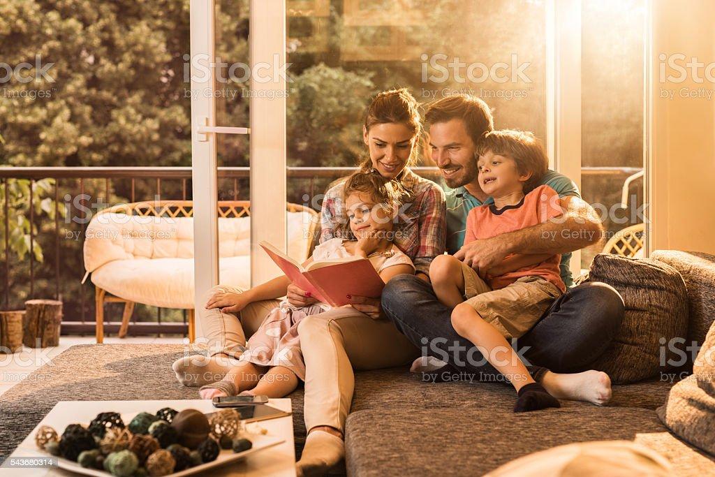 Glückliche Eltern beim Buchlesen mit ihren kleinen Kindern. – Foto