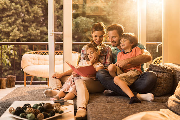 Happy parents reading a book with their small kids. stock photo