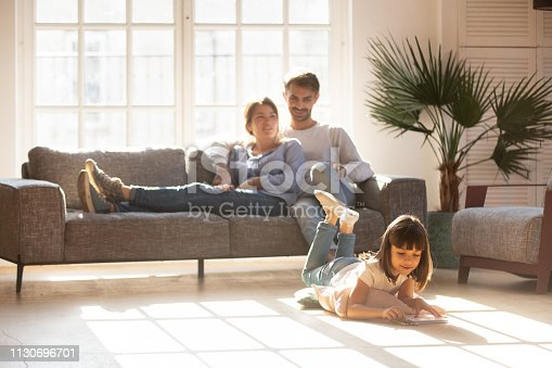 Happy parents relaxing on couch in comfort light living room while little kid child daughter playing on warm floor drawing with colored pencils, family having fun together, underfloor heating concept