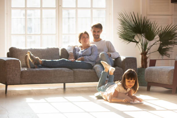 happy parents relaxing on couch while kid drawing on floor - casa imagens e fotografias de stock