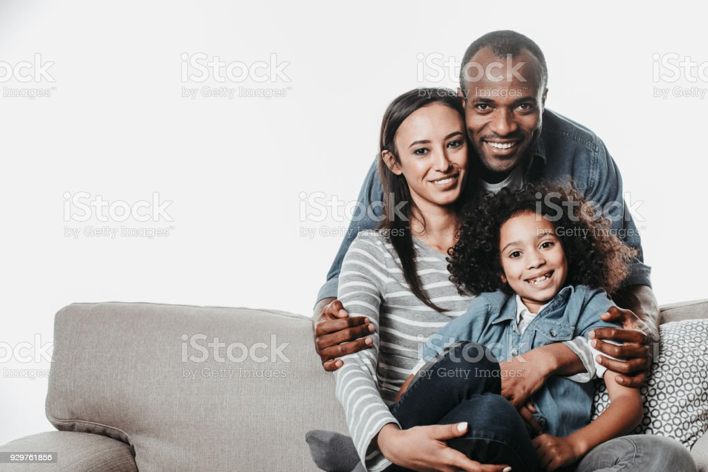 Happy parents resting with lovely child on divan stock photo