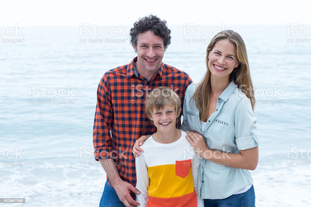 Happy parents standing with son by sea royalty-free stock photo