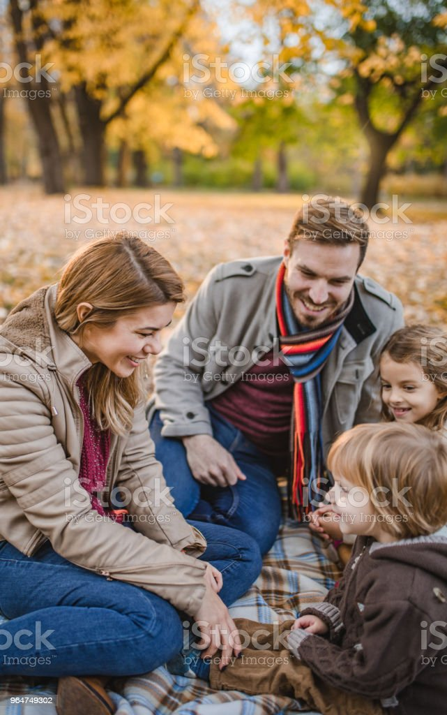 Happy parents talking to their small kids while relaxing in autumn day. royalty-free stock photo