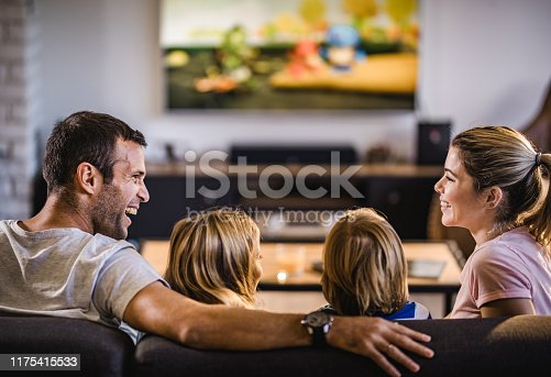 Young happy parents communicating while watching a movie with their small kids in the living room.