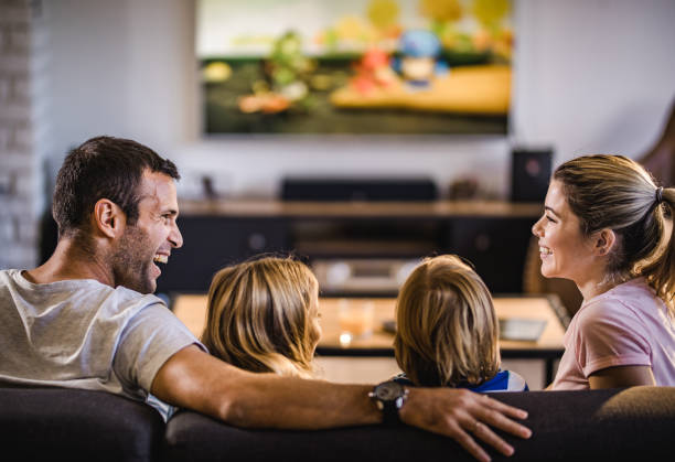 happy parents talking while watching tv with their kids at home. - televisor imagens e fotografias de stock