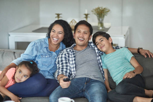 Happy parents watching TV with children at home stock photo
